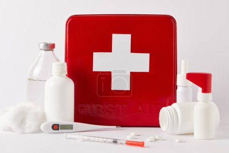 close-up shot of red first aid kit box with different medical bottles and supplies on white