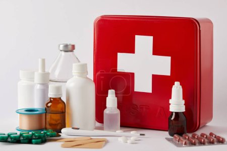 close-up shot of first aid kit box with different medical bottles and supplies on white