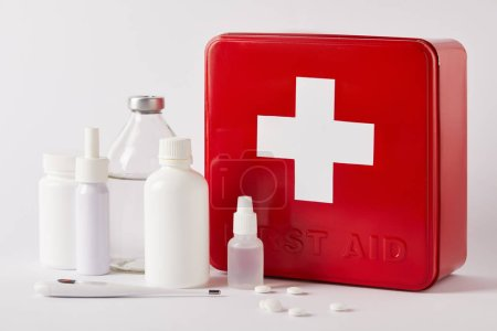 close-up shot of first aid kit box with different medical supplies on white