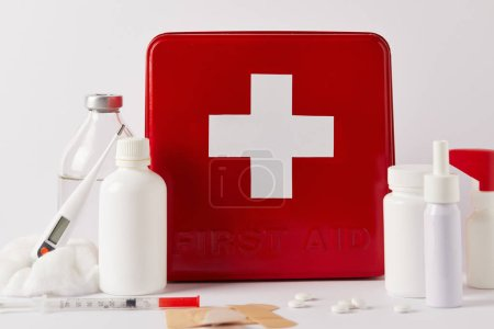 close-up shot of first aid kit box with various medical supplies on white
