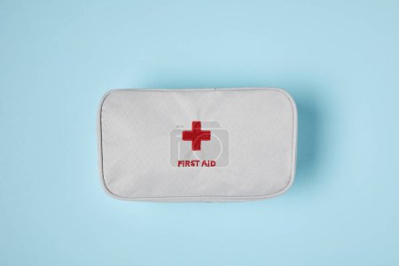 top view of white first aid kit bag on blue surface