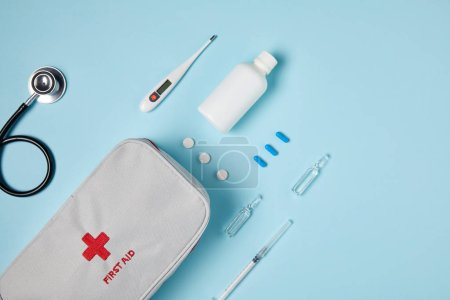 top view of white first aid kit bag with stethoscope and various medicines on blue surface