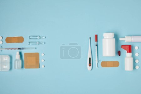 top view of composed various medical supplies on blue surface