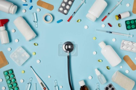 top view of stethoscope surrounded with various medicines on blue surface