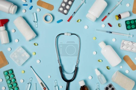 Photo for Top view of stethoscope surrounded with different medicines on blue surface - Royalty Free Image
