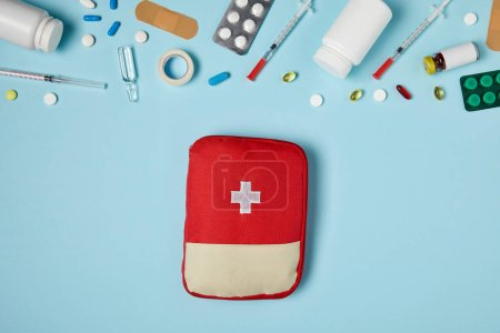 top view of red first aid kit bag on blue surface with different medicines