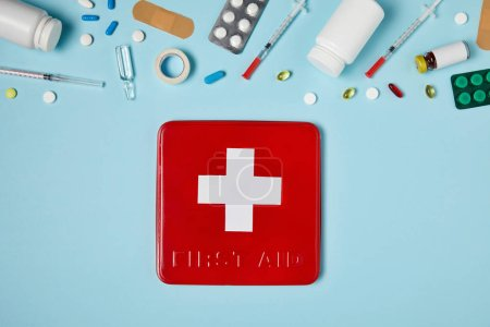 top view of red first aid kit box on blue surface with various medicines