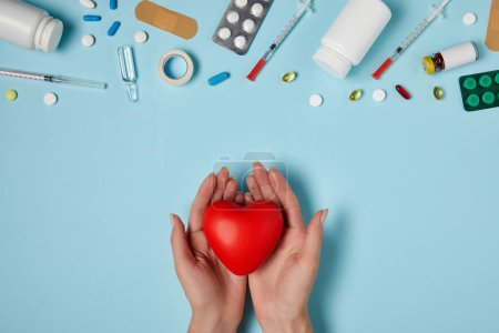 cropped shot of woman holding heart over medicines on blue surface