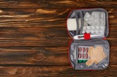 top view of opened first aid kit bag on wooden tabletop