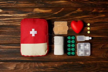 top view of first aid kit bag with medicines on wooden tabletop