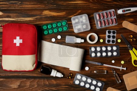 top view of first aid kit bag with various medicines on wooden tabletop