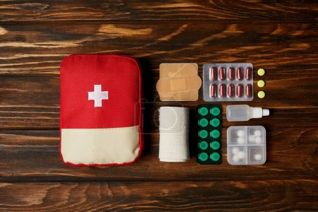 top view of first aid kit composed with various pills and bandage on wooden tabletop