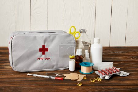 close-up shot of first aid kit with various medicines on wooden tabletop