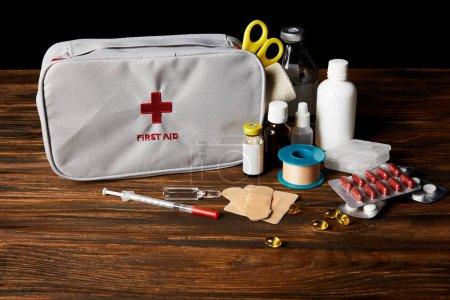 close-up shot of first aid kit with different medicines on wooden tabletop and on black