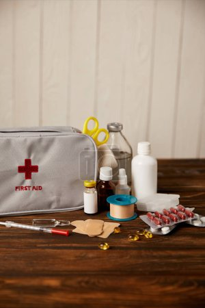 close-up shot of first aid kit with different medicines on wooden tabletop