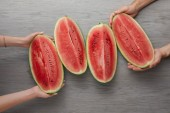 cropped shot of man and woman holding watermelon slices on grey wooden surface