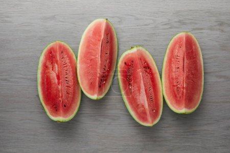 Photo pour Vue de dessus des tranches de pastèque fraîche disposés sur une surface en bois grise - image libre de droit