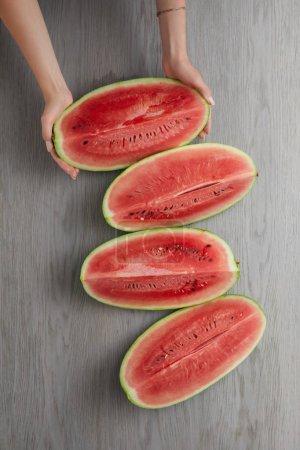 Photo pour Recadrée tir des mains féminines et des tranches de melon d'eau fraîche sur une surface en bois grise - image libre de droit