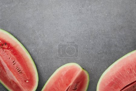 flat lay with arranged watermelon pieces on grey concrete tabletop