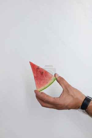 Photo for Cropped shot of man holding watermelon piece in hands on white surface - Royalty Free Image