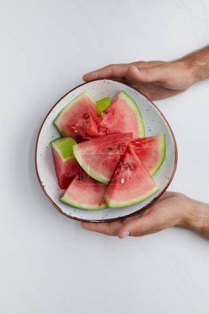 partial view of man holding bowl with watermelon pieces in hands on white surface