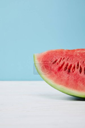 Photo for Close up view of fresh watermelon slice on white surface on blue background - Royalty Free Image