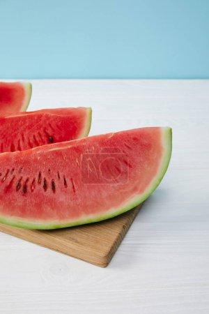 Photo pour Bouchent la vue des tranches de melon d'eau disposés sur une planche à découper sur une surface blanche sur fond bleu - image libre de droit