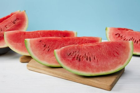 close up view of arranged watermelon slices on cutting board on white surface on blue backdrop
