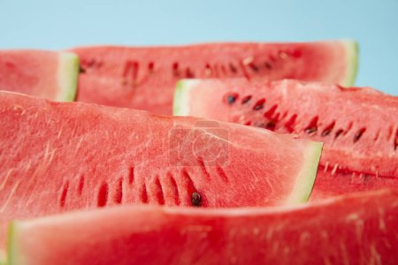 close up view of arranged watermelon slices on white surface on blue backdrop