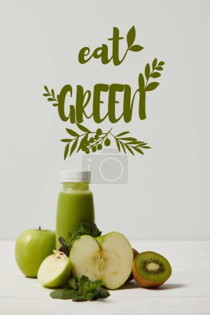 Photo for Green detox smoothie with apples, kiwi and mint and on white wooden surface, eat green inscription - Royalty Free Image