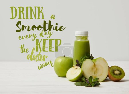 green detox smoothie with apples, kiwi and mint and on white wooden surface, drink smoothie everyday keep doctor away inscription