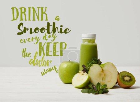 Photo pour Smoothie détox verte aux pommes, kiwi et menthe et sur bois surface, boisson smoothie garder tous les jours doctor away inscription blanche - image libre de droit