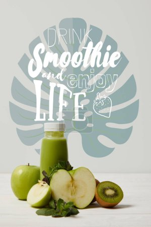 Photo for Green detox smoothie with apples, kiwi and mint and on white wooden surface, drink smoothie and enjoy life inscription - Royalty Free Image