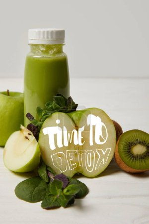 bottle of green detox smoothie with apples, kiwi and mint and on white wooden surface, time to detox inscription