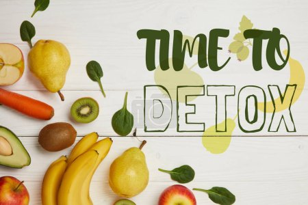 top view of fresh fruits and spinach leaves on white wooden background with copy space, time to detox inscription