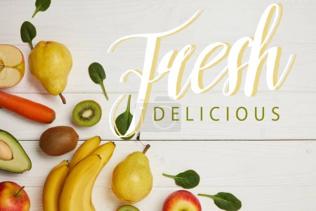 top view of fresh fruits and spinach leaves on white wooden background with copy space, fresh delicious inscription