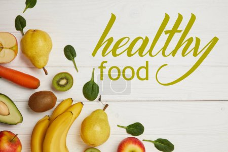 top view of fresh fruits and spinach leaves on white wooden background with copy space, healthy food inscription