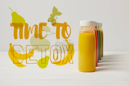 Photo for Organic detox smoothies in bottles standing in row, time to detox inscription - Royalty Free Image