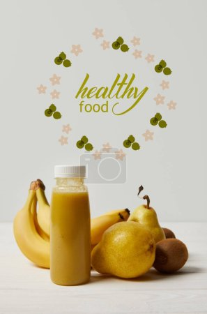 yellow detox smoothie in bottles with bananas, pears and kiwis on white background, healthy food inscription