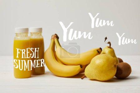Foto de Amarillo de desintoxicación batidos en botellas con plátanos, peras y kiwis en fondo blanco, inscripción de verano fresco - Imagen libre de derechos