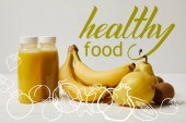 yellow detox smoothies in bottles with bananas, pears and kiwis on white background, healthy food inscription