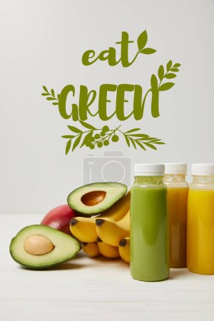 Photo for Fresh detox fruits and smoothies in bottles on white background, eat green inscription - Royalty Free Image