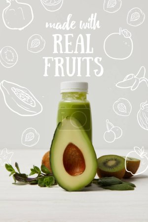 green detox smoothie with avocado, kiwi and mint on white wooden surface, made with real fruits inscription