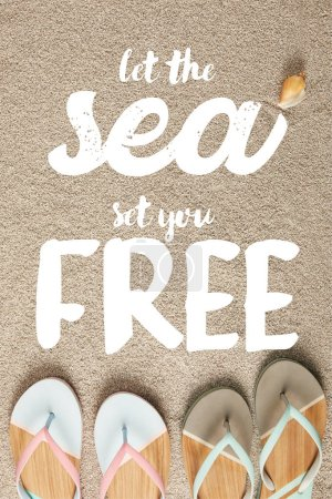 flat lay with summer flip flops and seashell on sand, let sea set you free inscription