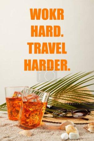 Photo pour Vue rapprochée de chapeau de paille, cocktails, coquillages, lunettes de soleil et feuille de palmier sur sable sur fond gris, travailler dur voyage inscription plus difficile - image libre de droit