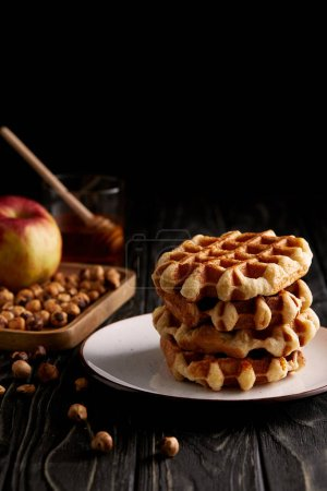 stack of belgian waffles on plate with hazelnuts and apple on black wooden table