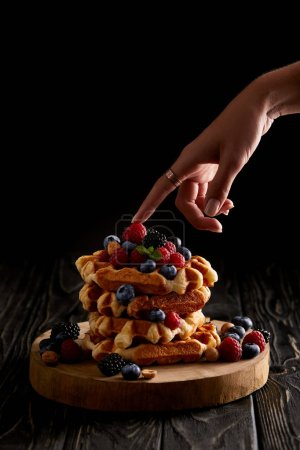 cropped shot of woman touching stack of belgian waffles with berries on black wooden table