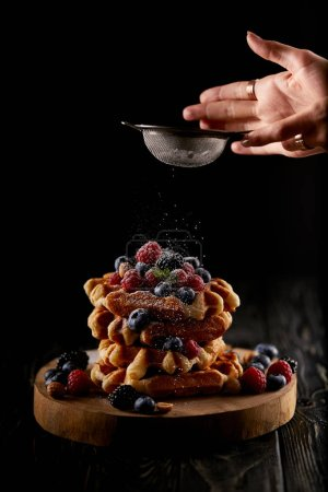 Photo for Cropped shot of woman spilling sugar powder onto belgian waffles through sieve on black - Royalty Free Image