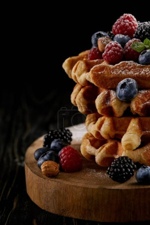 close-up shot of delicious belgian waffles with berries on wooden cutting board on black