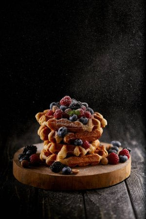 delicious belgian waffles with sugar powder spilling from side on black